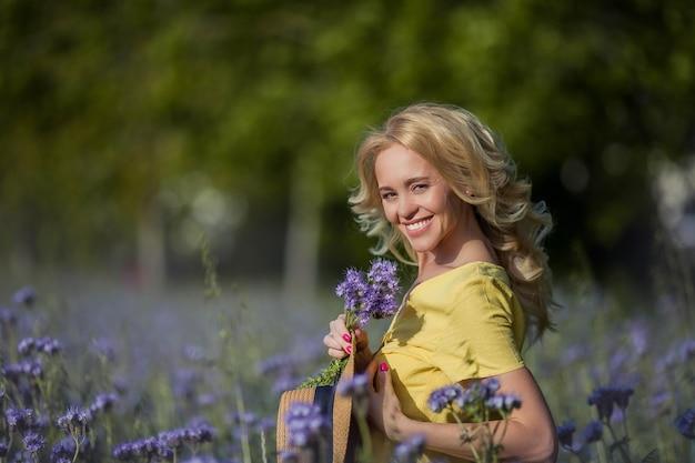 Молодая красивая женщина блондинка в шляпе идет через поле фиолетовых цветов. летом. весна.