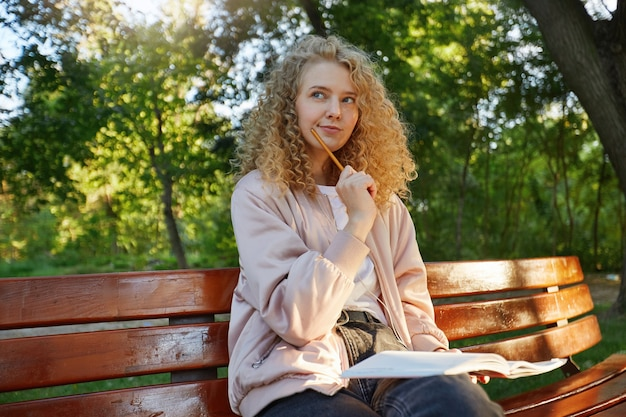 A young beautiful woman blonde sits on a park bench, with headphones and notepad, looks away