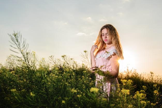 Young beautiful woman in a blue dress enjoying chamomile field among mountains. summer mood