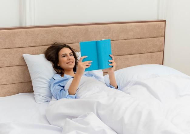 Giovane bella donna in pigiama blu posa sul letto che legge un libro che riposa godendosi il fine settimana nell'interno della camera da letto