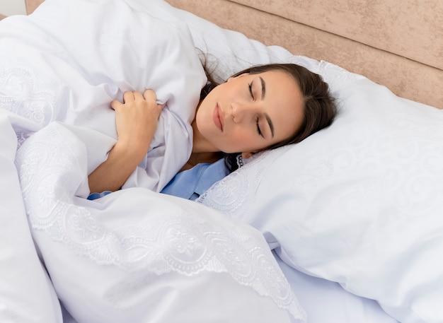 Giovane bella donna in pigiama blu che pone sul letto che riposa su morbidi cuscini che dorme pacificamente a casa nell'interno della camera da letto su sfondo chiaro
