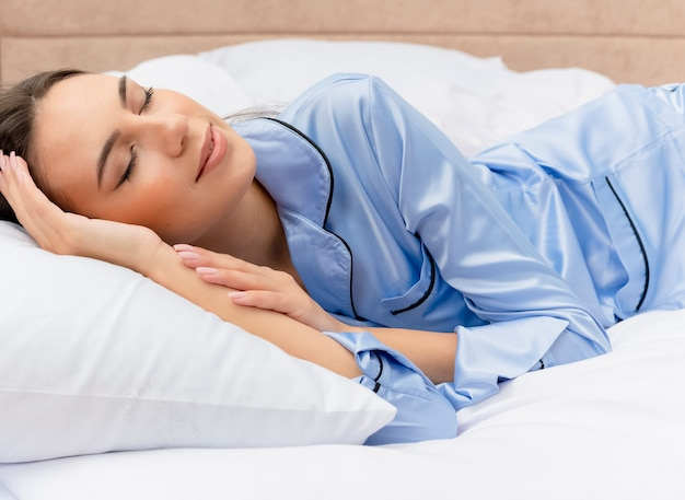 Young beautiful woman in blue pajamas laying on bed resting on soft pillows sleeping peacefully at home in bedroom interior on light background
