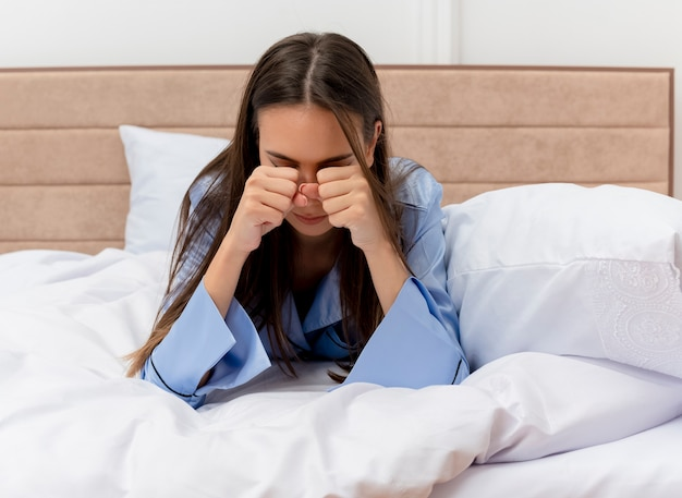 Young beautiful woman in blue pajamas laying on bed rubbing eyes yawning feeling morning fatigue in bedroom interior on light background