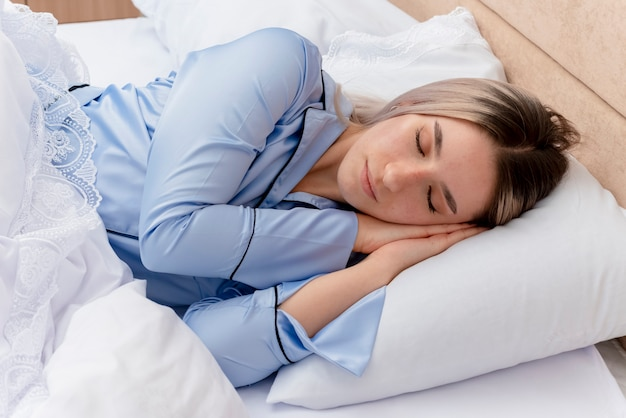 Young beautiful woman in blue pajamas laying on bed