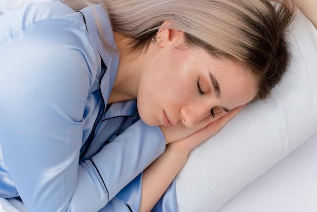Giovane bella donna in pigiama blu che pone sul letto