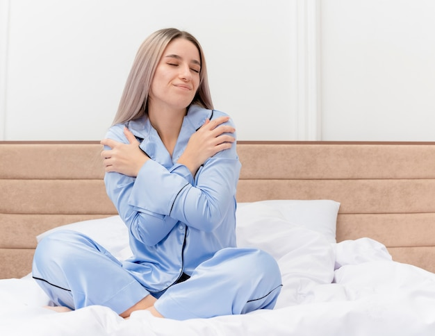Young beautiful woman in blue pajamas sitting on bed hugging herself with closed eyes feeling positive emotions in bedroom interior on light background
