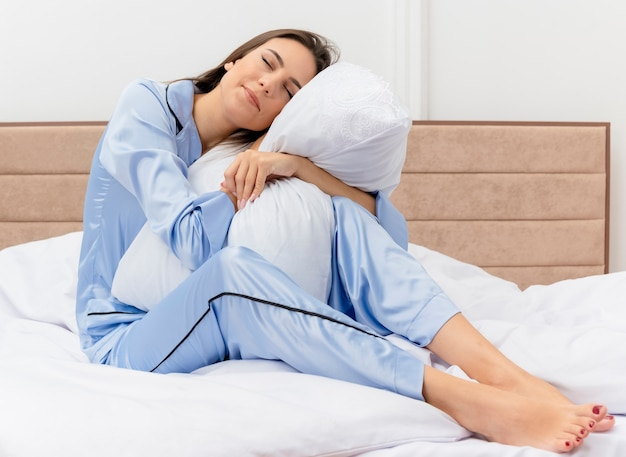 Young beautiful woman in blue pajamas sitting on bed hugging pillow feeling positive emotions with closed eyes in bedroom interior