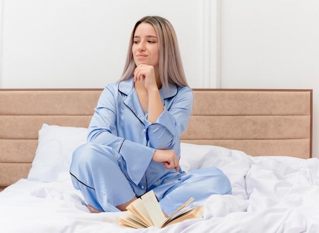 Giovane bella donna in pigiama blu seduta sul letto che guarda da parte con la mano sul mento pensando all'interno della camera da letto