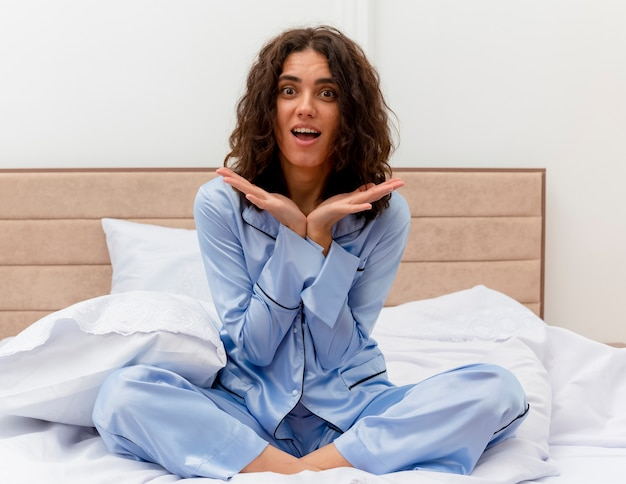 Young beautiful woman in blue pajamas sitting on bed looking at camera happy and surprised in bedroom interior on light background
