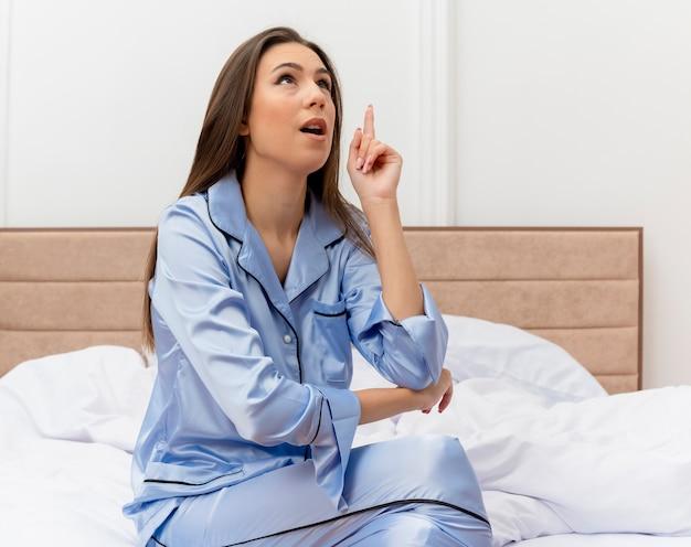 Giovane bella donna in pigiama blu che si siede sul letto che osserva in su amzed che mostra il dito indice che ha grande idea nell'interno della camera da letto su fondo chiaro