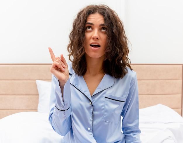 Giovane bella donna in pigiama blu che si siede sul letto che osserva in su che mostra il dito indice con il sorriso sul viso all'interno della camera da letto su sfondo chiaro