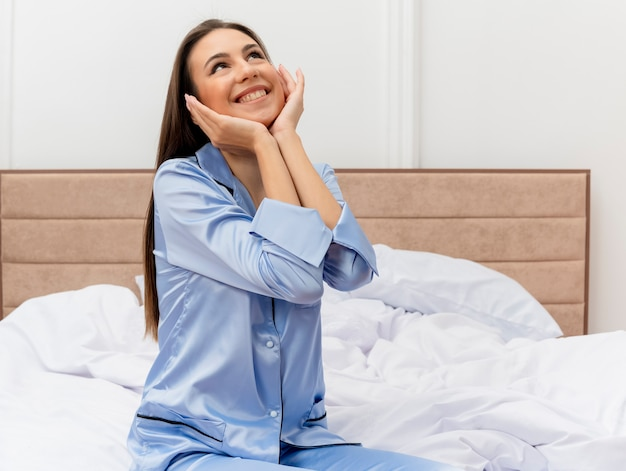Young beautiful woman in blue pajamas sitting on bed looking up with arms on face smiling cheerfully in bedroom interior on light background