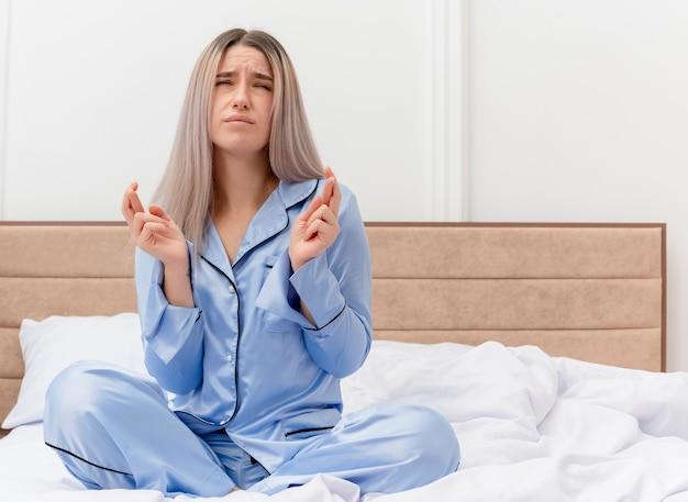Giovane bella donna in pigiama blu seduta sul letto che esprime il desiderio desiderabile incrociando le dita con l'espressione di speranza nell'interno della camera da letto