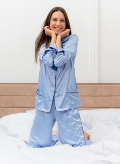 Giovane bella donna in pigiama blu seduta sul letto che riposa godendosi il fine settimana felice e positivo sorridendo allegramente nell'interno della camera da letto