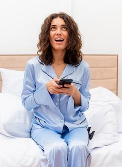 Giovane bella donna in pigiama blu che si siede sul letto utilizzando smartphone sorridente felice ed emozionato nell'interiore della camera da letto su sfondo chiaro