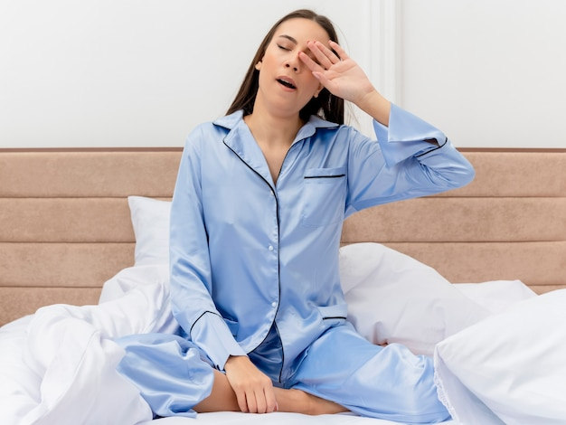 Young beautiful woman in blue pajamas sitting on bed waking up feeling morning fatigue yawning in bedroom interior on light background