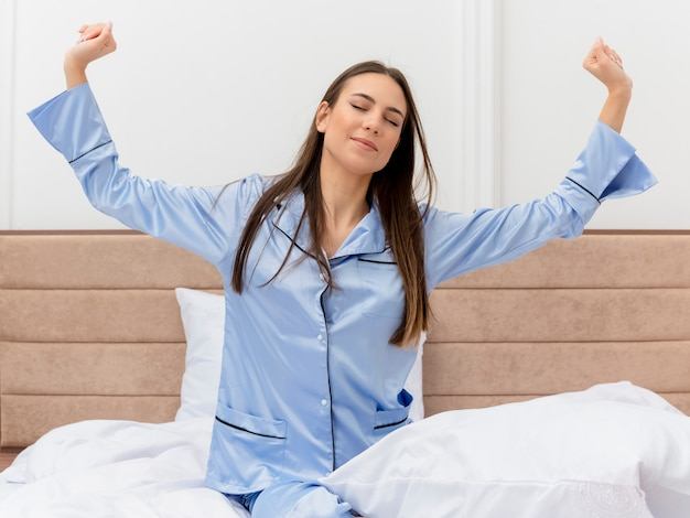 Young beautiful woman in blue pajamas sitting on bed waking up stretching hands enjoying morning time in bedroom interior