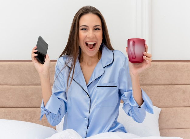 Young beautiful woman in blue pajamas sitting on bed with cup of coffee holding smartphone looking at camera happy and excited in bedroom interior on light background