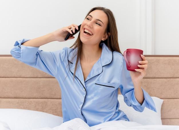 Giovane bella donna in pigiama blu che si siede sul letto con la tazza di caffè che tiene smartphone che guarda l'obbiettivo felice ed emozionato parlando al telefono cellulare all'interno della camera da letto su sfondo chiaro