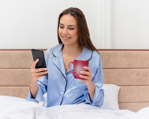 Giovane bella donna in pigiama blu che si siede sul letto con una tazza di caffè utilizzando smartphone guardandolo con il sorriso sul viso all'interno della camera da letto su sfondo chiaro