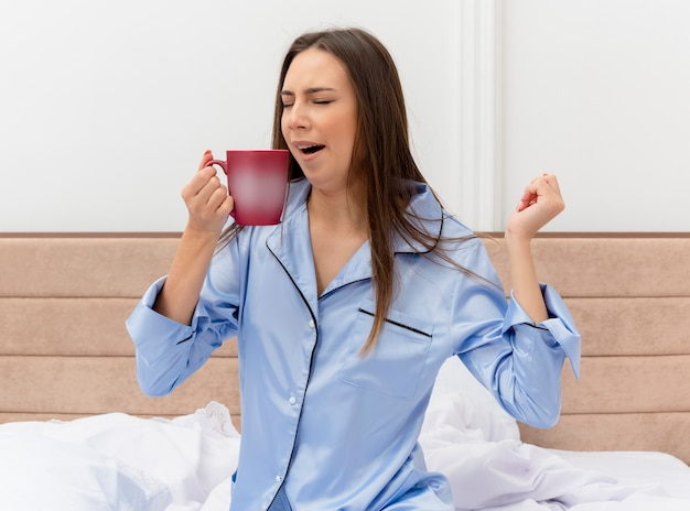 Young beautiful woman in blue pajamas sitting on bed with cup of coffee waking up yawning in bedroom interior on light background