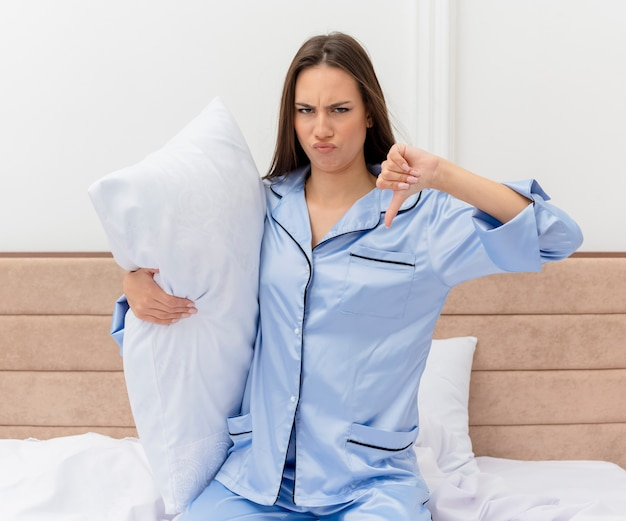 Young beautiful woman in blue pajamas sitting on bed with pillow being displeased showing thumbs down in bedroom interior