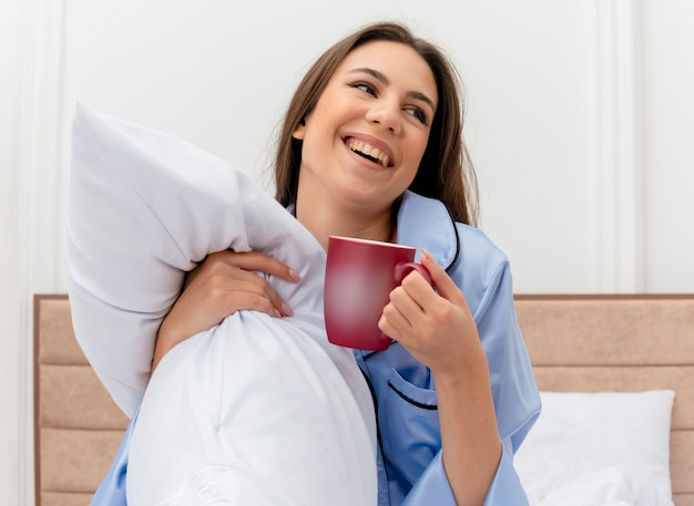 Young beautiful woman in blue pajamas sitting on bed with pillow and cup of coffee looking aside smiling cheerfully in bedroom interior on light background