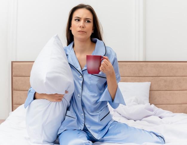 Giovane bella donna in pigiama blu che si siede sul letto con il cuscino e la tazza di caffè che osserva da parte con la faccia infelice essendo scontento nell'interno della camera da letto su sfondo chiaro