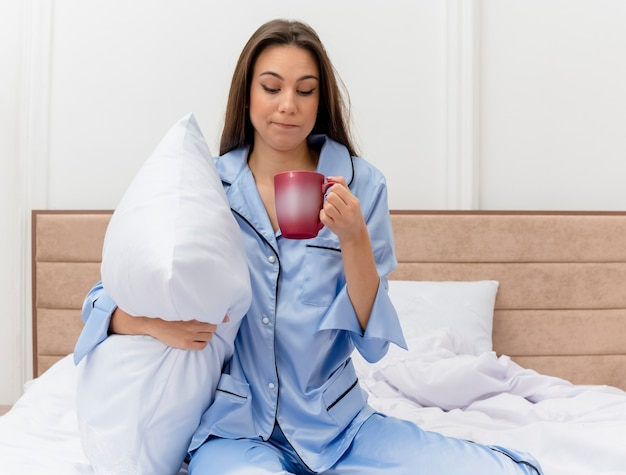 Young beautiful woman in blue pajamas sitting on bed with pillow and cup of coffee waking up feeling morning fatigue in bedroom interior on light background