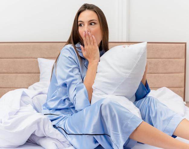 Giovane bella donna in pigiama blu che si siede sul letto con il cuscino che osserva da parte essere scioccato che copre la bocca con la mano all'interno della camera da letto su sfondo chiaro