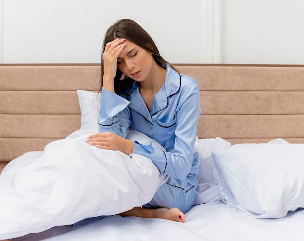 Young beautiful woman in blue pajamas sitting on bed with pillow looking unwell touching her head having headache in bedroom interior