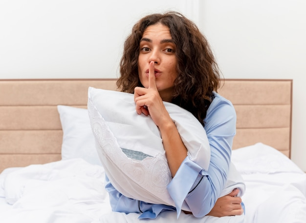 Young beautiful woman in blue pajamas sitting on bed with pillow making silence gesture with finger on lips in bedroom interior on light background