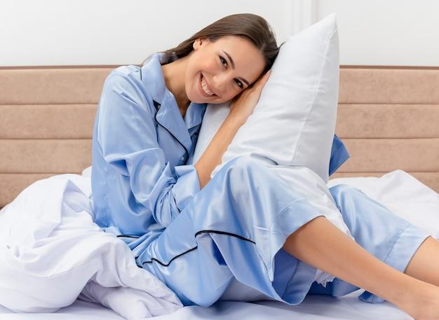 Giovane bella donna in pigiama blu che si siede sul letto con il cuscino che riposa che guarda l'obbiettivo sorridente felice e positivo che gode del fine settimana nell'interno della camera da letto su fondo chiaro