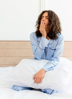 Young beautiful woman in blue pajamas sitting on bed with pillow waking up yawning in bedroom interior on light background