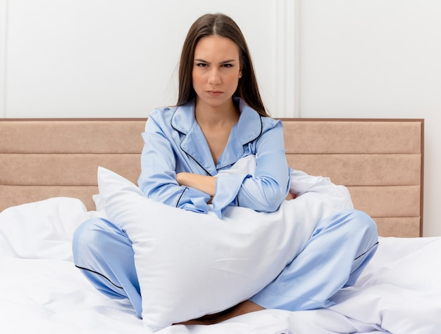 Young beautiful woman in blue pajamas sitting on bed with pillow with serious face being displeased in bedroom interior