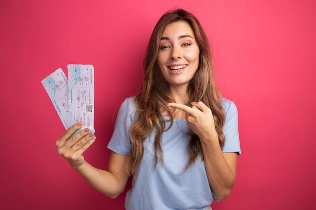 Giovane bella donna in maglietta blu che tiene i biglietti aerei che indica con il dito indice sorridendo allegramente