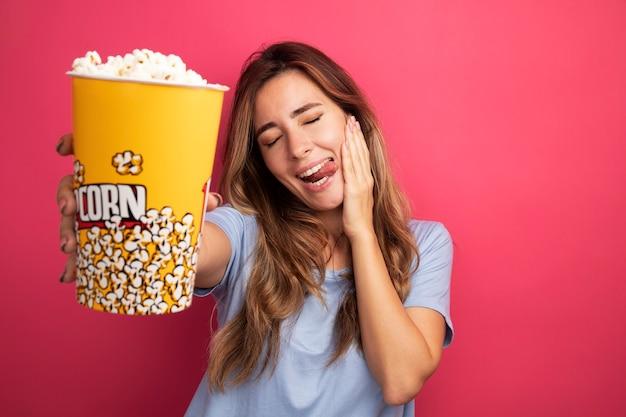 Giovane bella donna in maglietta blu che tiene secchio con popcorn allegro e positivo che tira fuori la lingua