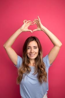 Giovane bella donna in maglietta blu che fa il gesto del cuore sopra la sua testa sorridendo allegramente