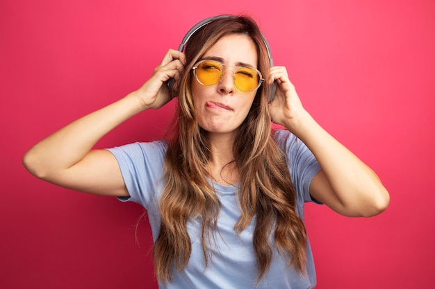 Young beautiful woman in blue t-shirt wearing yellow glasses with headphones looking aside happy and joyful sticking out tongue standing over pink background