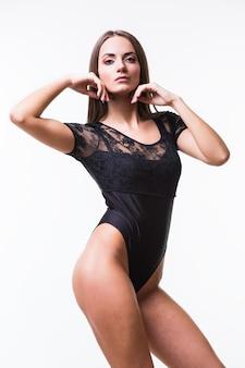 Corpo di giovane bella donna su sfondo grigio in abiti sportivi neri