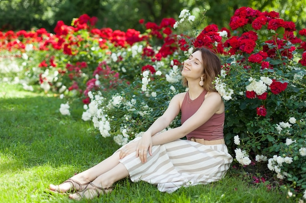 A young beautiful woman in boho clothing is sitting under a bush of scarlet roses.