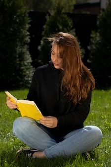 Young beautiful woman book lover resting outdoors reading