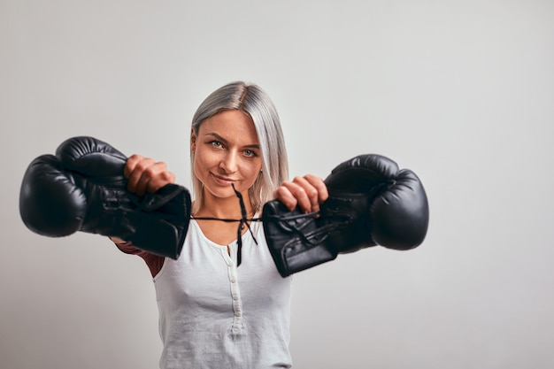Young beautiful woman boxer posing with black boxing gloves in her hands on a grey
