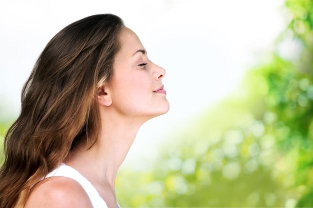 흐릿한 배경으로 야외에서 호흡하는 젊은 아름다운 여성
