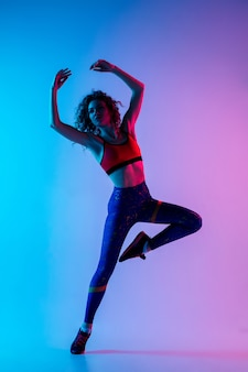 Young beautiful woman in bright sportwear isolated on gradient pink-blue background in neon light.