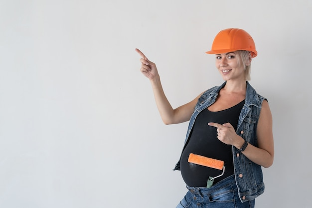 Young beautiful woman builder in an orange protective helmet on her head. pregnant girl. holding a paint roller points up with a finger to an empty space for text