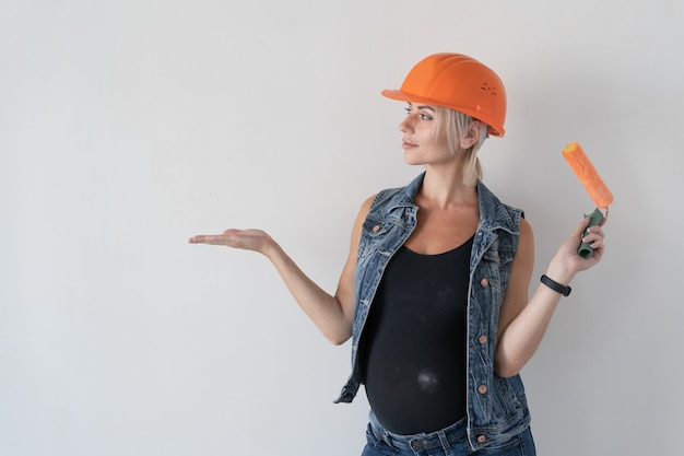 Young beautiful woman builder in an orange protective helmet on her head. pregnant girl. holds a paint roller looks at the empty space for the text.