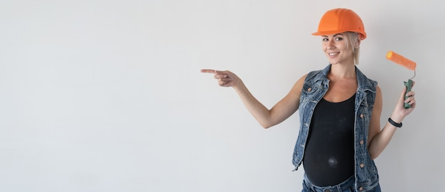 Young beautiful woman builder in an orange protective helmet on her head. pregnant girl. holds a paint roller points with a finger at an empty space for text