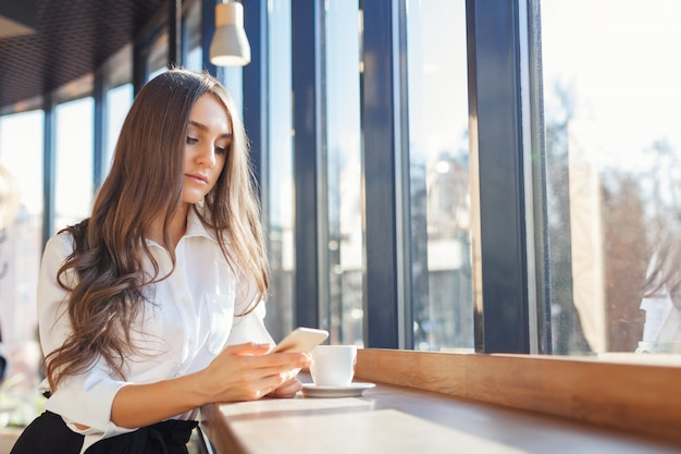 Young beautiful woman in business clothes use smartphone in a cafe
