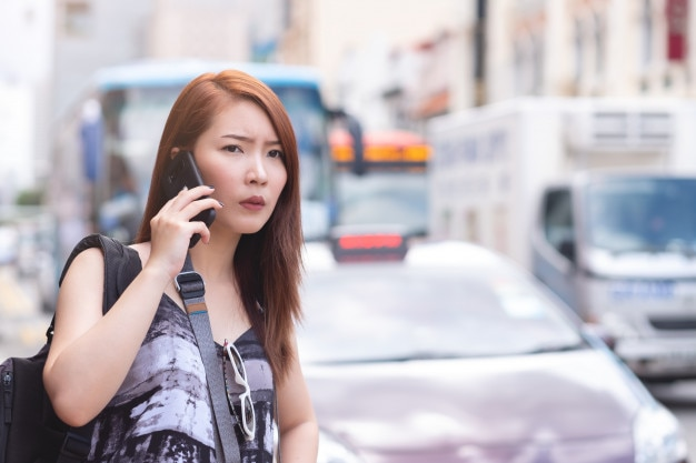 Young beautiful woman calling public taxi by phone in singapore. standing beside the road